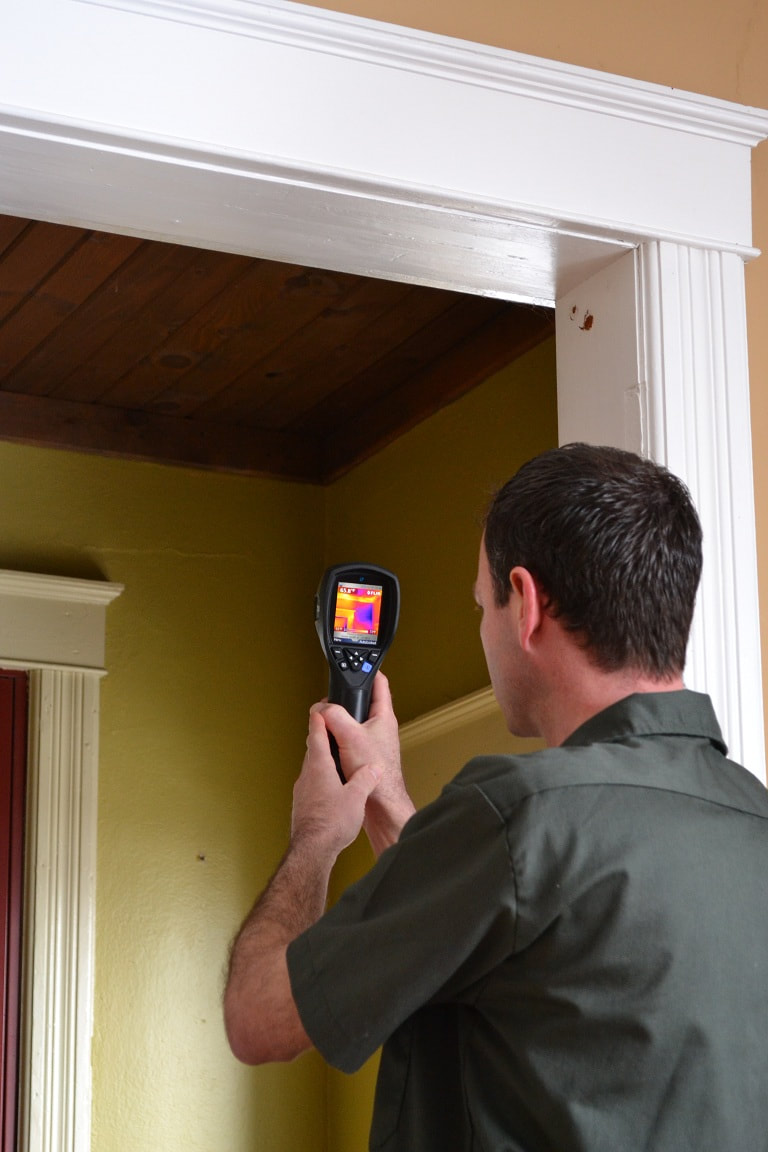 A home inspector uses a thermal camera to inspect home insulation in a home in Stow Ohio